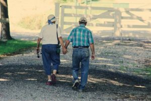 Old couple walking and thinking about downsizing in retirement